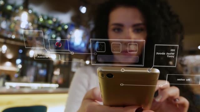 schöne mädchen mit lockigen haaren in einem restaurant nutzt smartphone mit holographischen schnittstelle - holografisch stock-videos und b-roll-filmmaterial