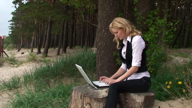 Hermosa Chica con ordenador portátil en el bosque - vídeo