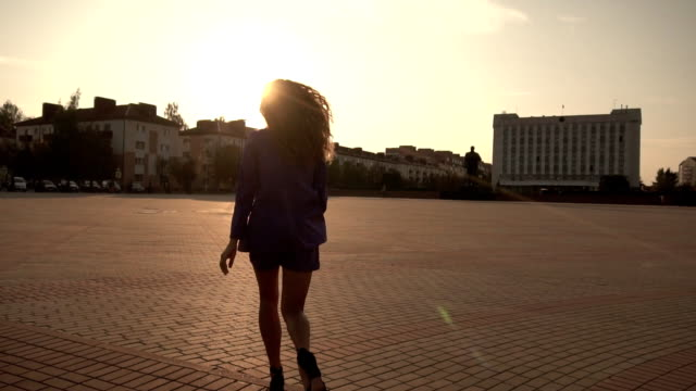 a beautiful girl with long curly hair runs around the city and turns around, looks at the camera against the sunset, slow-mo - сбежавший из дома стоковые видео и кадры b-roll