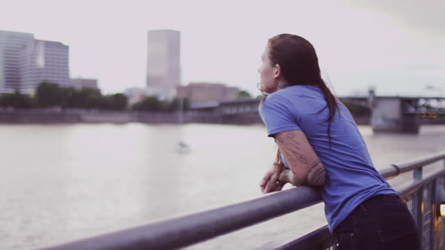 A beautiful girl with long hair looking at a city across the river, slow motion