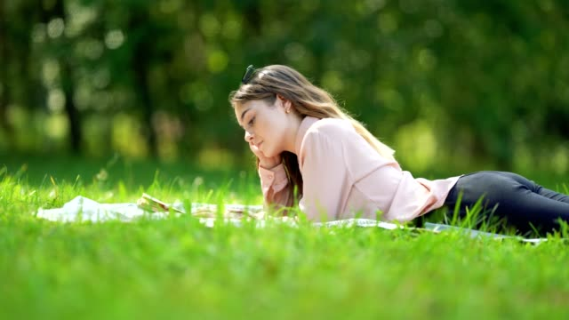 vídeos de stock, filmes e b-roll de uma garota bonita com cabelo comprido lê um livro, deitado na grama do parque em um dia ensolarado - 16 17 anos