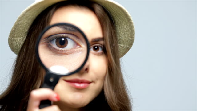 Beautiful girl with loupe zooming her eye Girl looking through a magnifying glass. Beautiful girl with loupe zooming her eye magnifying glass stock videos & royalty-free footage