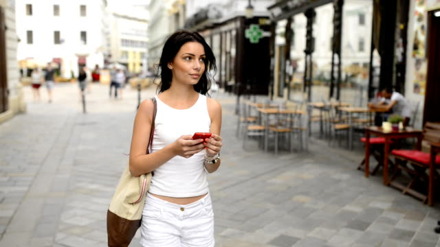 Beautiful girl with mobile phone as navigation on the street. video