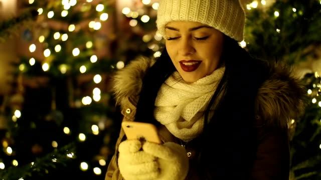 vídeos de stock, filmes e b-roll de linda garota com o celular na rua com luzes de natal - câmera lenta no inverno - feriado evento