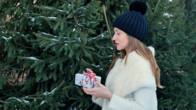 Beautiful girl with red lips holds a festive gift at fir-tree background Beautiful girl with red lips holds a festive christmas gift in hands and posing for camera at the fir-tree background. Cute female in black hat touches the branches with snow on it. The snow falls down from the tree. red lipstick stock videos & royalty-free footage