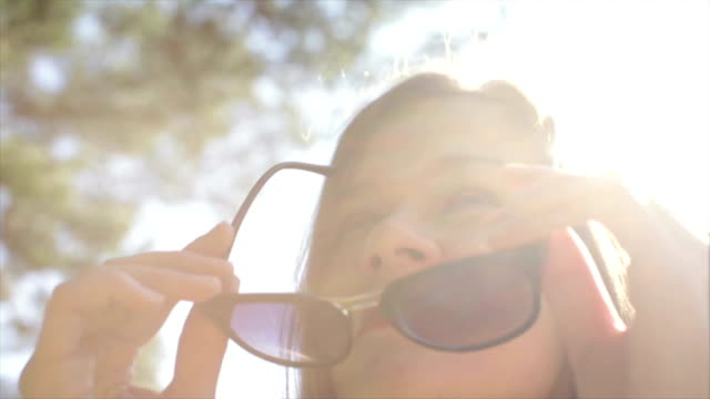 Beautiful girl with red lips wears sunglasses outdoors glasses and looking up, enjoying the sun. Sunlight creates a rainbow reflection in the frame. Her sunglasses reflect trees and blue sky. video