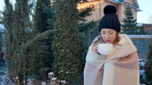 Beautiful girl wrapped in plaid drinks a hot tea to warm at winter outdoors video