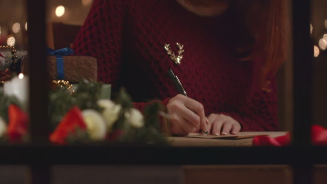 a beautiful girl writes a christmas letter to her friends. - postcard стоковые видео и кадры b-roll