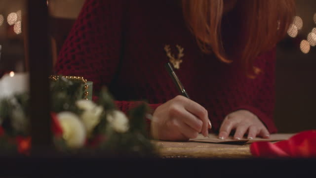 Beautiful girl writes a letter to Santa Claus.