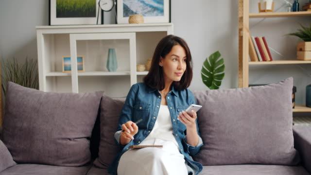 bella ragazza che scrive nel taccuino guardando lo schermo dello smartphone seduto a casa - divano video stock e b–roll