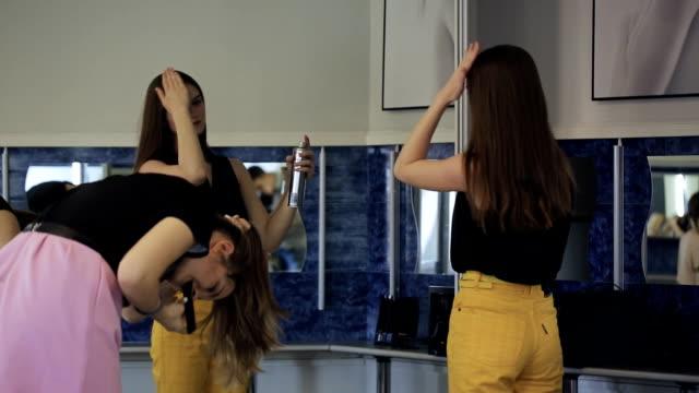Beautiful girls create fashionable hairdo using hair spray video