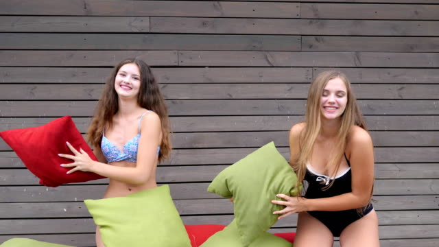 Beautiful Girls in swimsuits played with colored pillows, Lovely girlfriends have good time video