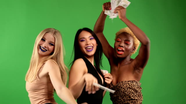 Beautiful Girls White European,Asian and Black African American Sexy young womens with Natural Healthy Skin Smiling on an isolated background.Dancing and scattering dollars.Party fun and happiness