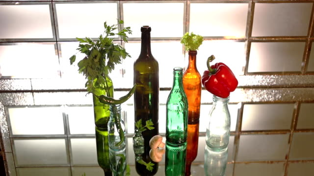 beautiful glass bottle with vegetables and herbs are on the mirror surface - paprica video stock e b–roll