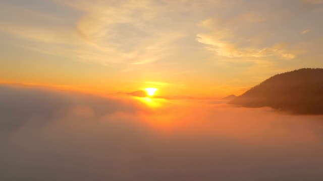 AERIAL: Beautiful golden sunset sun setting above the misty clouds AERIAL: Beautiful golden sunset sun setting above the misty clouds horizon over land stock videos & royalty-free footage