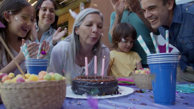 彼女の家族が彼女のすべての笑顔の隣で祝うように彼女の誕生日のろうそくを吹き消す美しい祖母 - 老夫婦点の映像素材/bロール