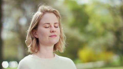 vídeos de stock e filmes b-roll de beautiful green park helps stressed woman to calm down - desfocado focagem