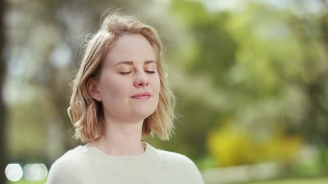 vídeos de stock, filmes e b-roll de o parque verde bonito ajuda a mulher forçada a acalmar-se para baixo - desfocado foco