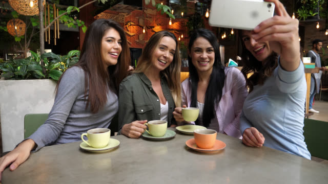 beautiful group of latin american friends at a coffee shop enjoying a warm drink and taking a selfie with smartphone - trentenne video stock e b–roll