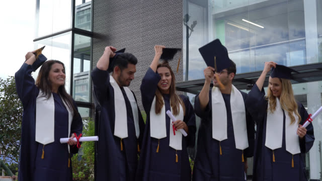 beautiful group of students throwing their graduation caps excited celebrating - кепка стоковые видео и кадры b-roll