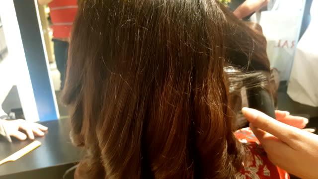 髪を瀕死の後、ヘアサロンでハイライトを作る若い女性の美しい髪型。 ビデオ