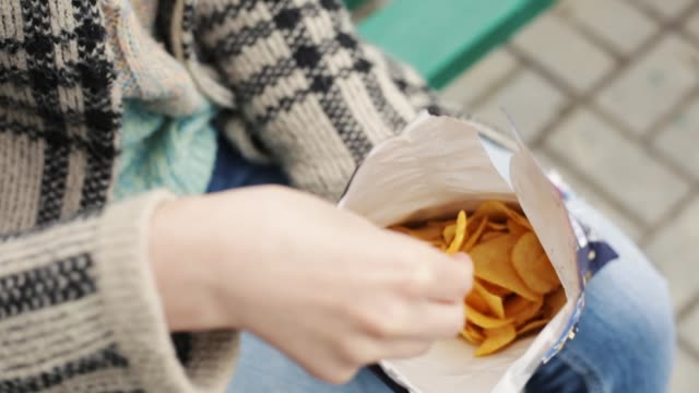 Beautiful hands of woman take potato chips Beautiful hands of woman take potato chips. Outdoors, closeup shot. snack stock videos & royalty-free footage