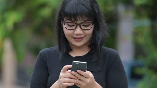 vídeos y material grabado en eventos de stock de hermosa empresaria asiática feliz con teléfono en las calles al aire libre - sudeste