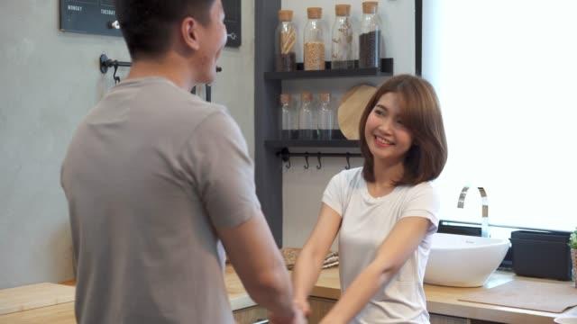 stockvideo's en b-roll-footage met mooie gelukkige aziatische paar dansen in de keuken thuis. jonge aziatische echtpaar heeft romantische tijd tijdens het luisteren muziek thuis. - oost aziatische cultuur