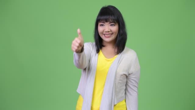 vídeos y material grabado en eventos de stock de hermosa mujer asiática feliz sonriendo mientras los pulgares - sudeste
