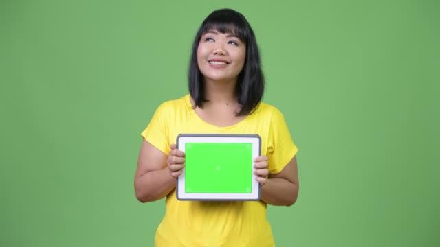 beautiful happy asian woman thinking while showing digital tablet - юго восток стоковые видео и кадры b-roll