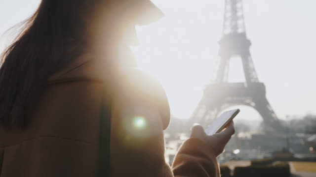 schöne glückliche bloggerin frau mit telefon social network app zu fuß auf hinterleuchtet sonnigen eiffelturm blick zeitlupe. - wahrzeichen stock-videos und b-roll-filmmaterial