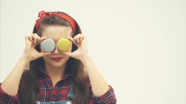 Beautiful happy cute young pretty woman hiding her eyes behind cake macaroons sweeties.
