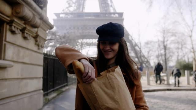 beautiful happy european woman walking near eiffel tower, giving a piece of french baguette to camera man slow motion. - francuska kuchnia filmów i materiałów b-roll