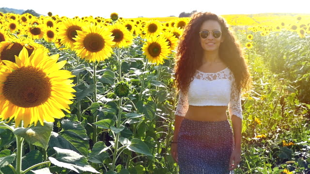 Beautiful happy girl woman walking at sunflower field in sunset. Freedom concept. Slow motion