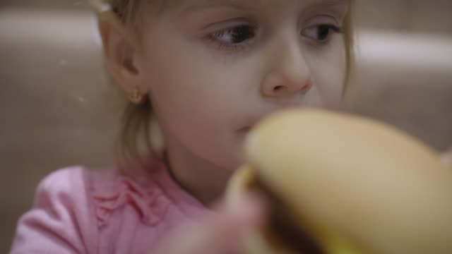 beautiful happy hungry baby girl eating hamburger. concept child with fast food - obsoleto video stock e b–roll