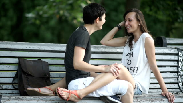 beautiful happy lesbians relaxing on bench in park - kids kiss embarrassed video stock e b–roll