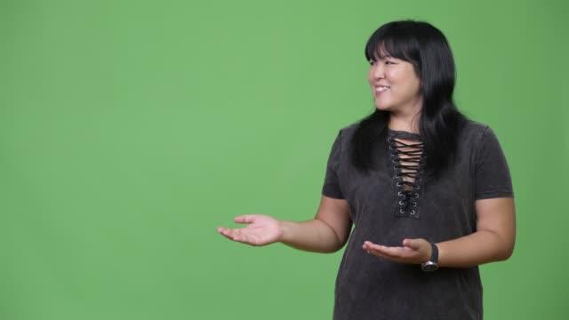 vídeos y material grabado en eventos de stock de hermosa mujer asiática con sobrepeso feliz mostrando algo - sudeste