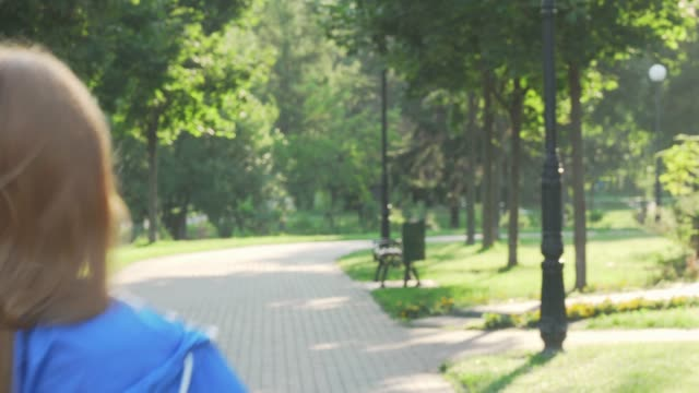 Beautiful happy sportswoman smiling to the camera while running in the park
