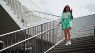 istock A beautiful happy woman in glasses and fashionable clothes turquoise color with a mobile phone in hand is going down the stairs business center, smiling and laughing with joy of success. Slow motion. 1280970737