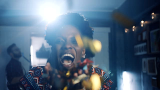 Beautiful happy young African woman laughing, blowing on confetti at fun atmospheric celebration party slow motion. video