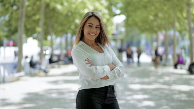 Beautiful happy young woman posing on street Beautiful happy young woman posing on street. Attractive young woman standing with hands on waist and smiling at camera outdoor. Beauty concept arms akimbo stock videos & royalty-free footage