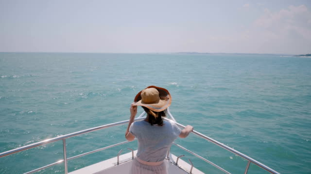 beautiful high angle back view shot of happy successful tourist woman enjoying amazing sunny sea sail on yacht boat nose. - cappello video stock e b–roll