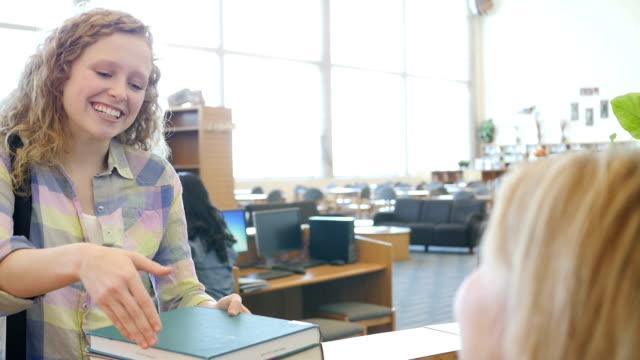 Hermosa estudiante de secundaria tomar libros de biblioteca mostrador de check-out en la habitación moderna, con Bibliotecario estrechándose las manos - vídeo