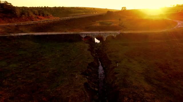 Beautiful hills on sunset. Woman walking along old-fashioned stone bridge