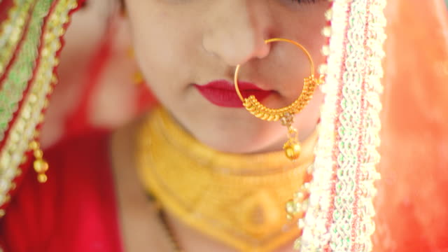 Beautiful Hindu bride in traditional dress looks at the camera. Indoor close-up 4k video of an Asian/Indian beautiful Hindu bride looks at the camera with a blank expression and holds her veil. She is in her jewelry with traditional Indian wedding dress, which is sari. indian culture stock videos & royalty-free footage