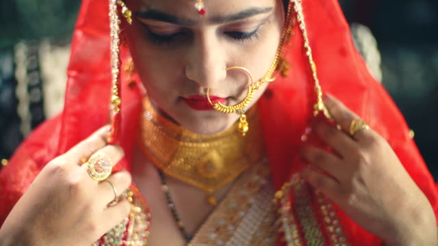 Beautiful Hindu bride in traditional dress looks at the camera.