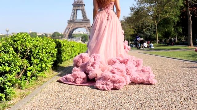 vídeos y material grabado en eventos de stock de hermosa chica hipster vestida para impresionar en un vestido de salón de baile rosa pastel posando para video shot con torre eiffel en el fondo - moda parisina