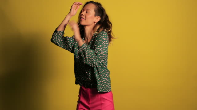 Beautiful Hipster Woman Dancing A close-up shot of a beautiful mixed race woman dancing in front of a yellow background, she is wearing fashionable clothing while having fun. background color stock videos & royalty-free footage