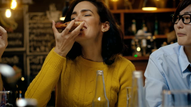 vídeos de stock e filmes b-roll de beautiful hispanic woman eats pizza slice at the stylish restaurant. she's surrounded by her friends. - pizza