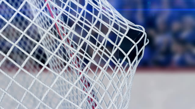 beautiful hockey puck flies into the gates grid in slow motion on stadium background. ice-hockey 3d animation of the goal moment. sport concept. - hockey stock videos and b-roll footage